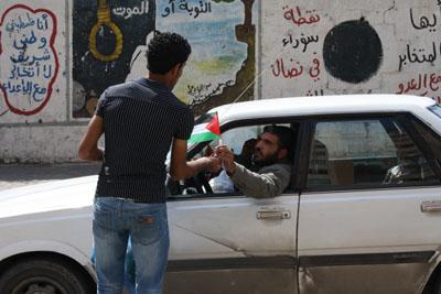 صورة برعاية بال ثينك للدراسات الاستراتيجية: العمال يوزعون اعلام فلسطين تعزيزاً للمصالحة
